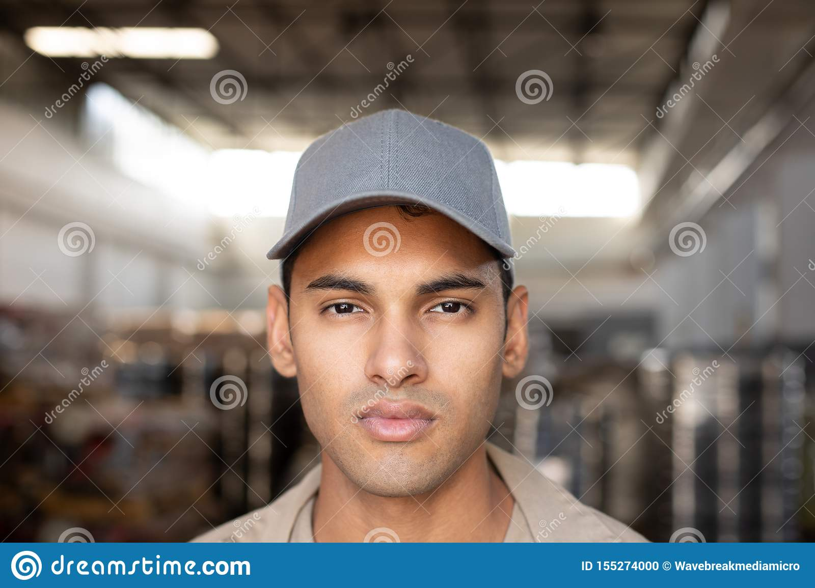Male worker looking at camera in warehouse