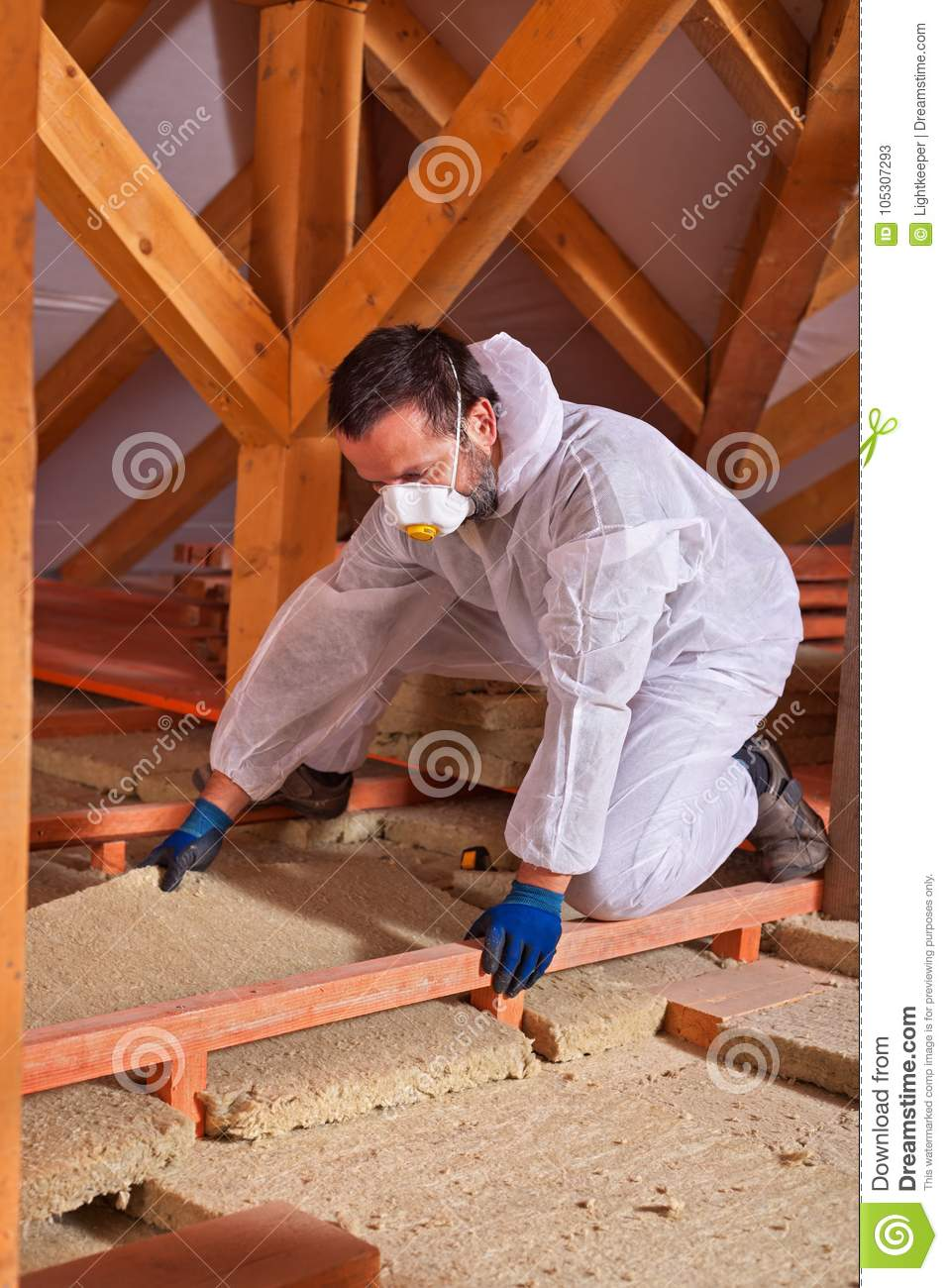 Male worker placing a rock wool thermal insulating panel between