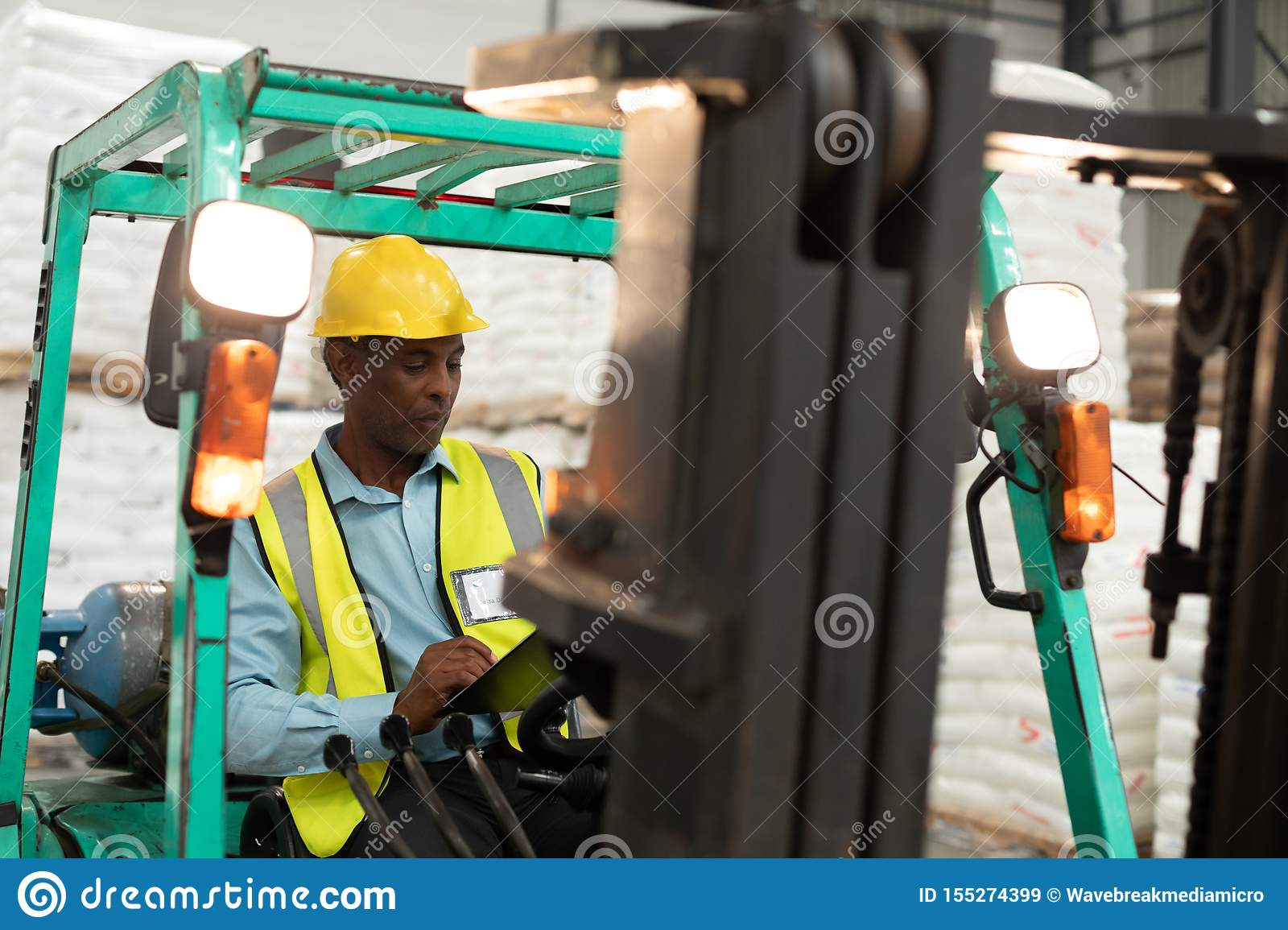 Male worker sitting in forklift and writing on clipboard in warehouse