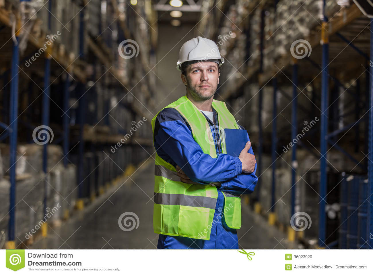 Male worker standing between selves with notebook