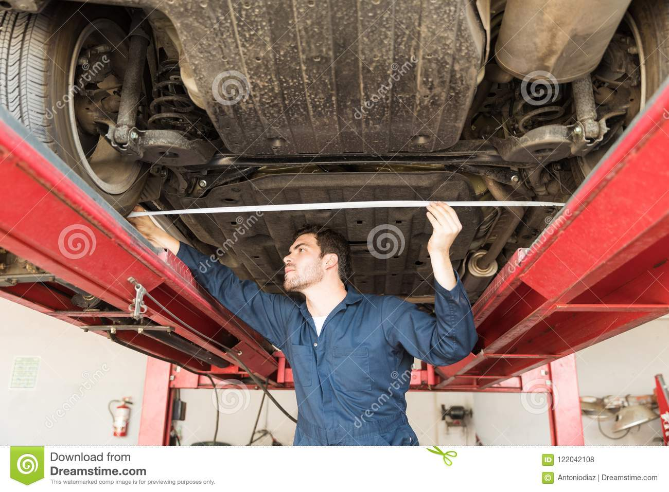 Male Worker Using Tape Measure To Check Wheel Alignment