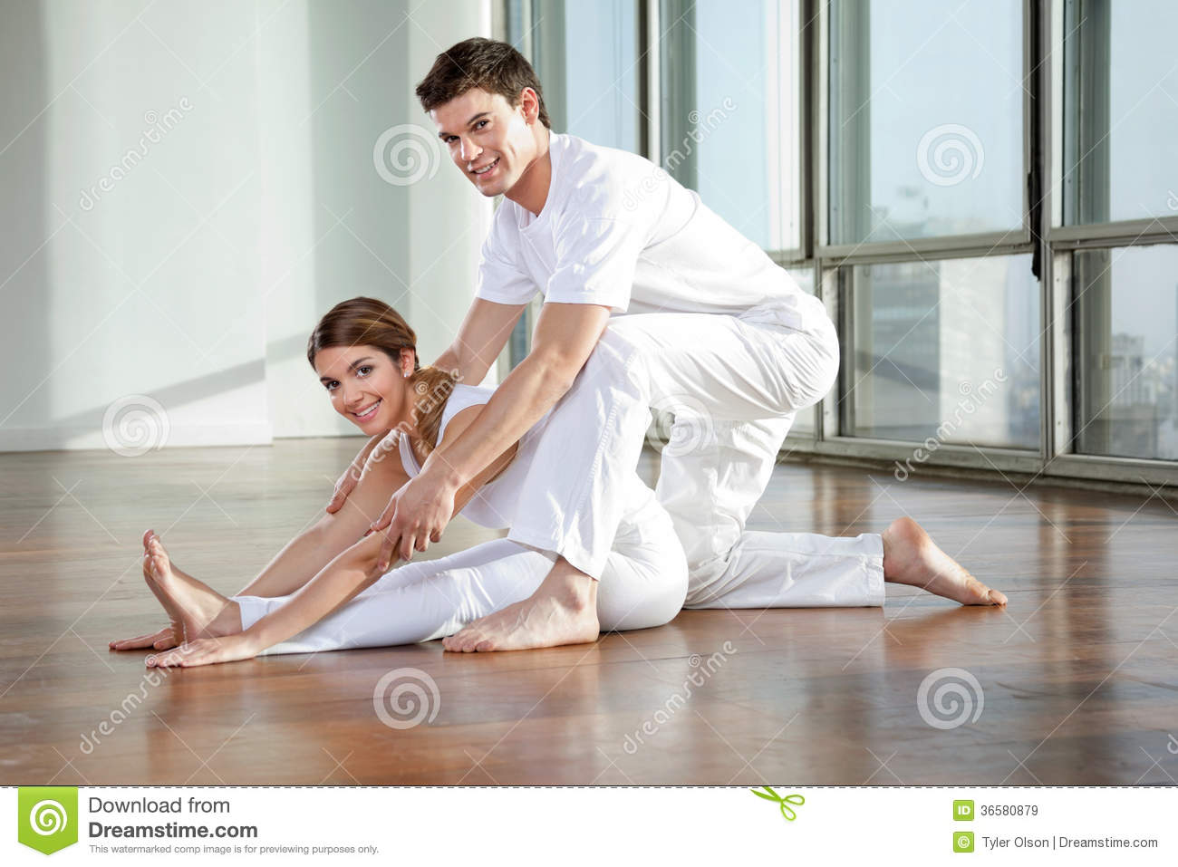 Male Yoga Instructor Assisting Woman Royalty Free Stock