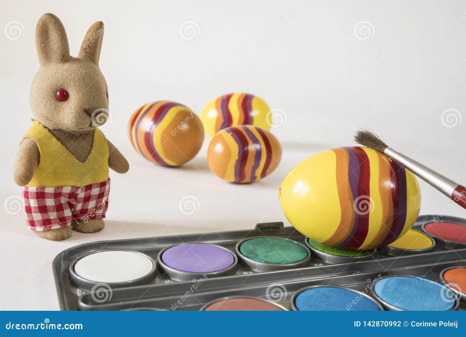 Malende Ostereier mit roter Bürste Osterhase und gelbe Eier