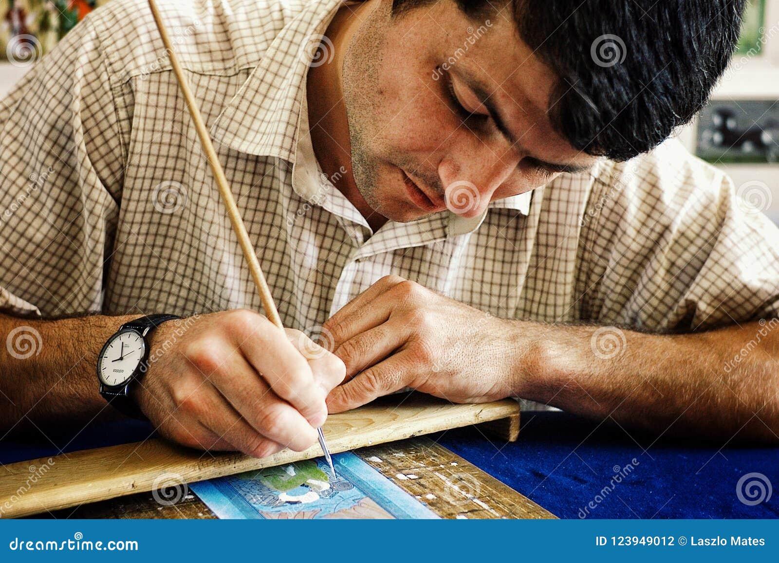 Malender Künstler arbeitet an einer kleinen Szene an seiner Werkstatt