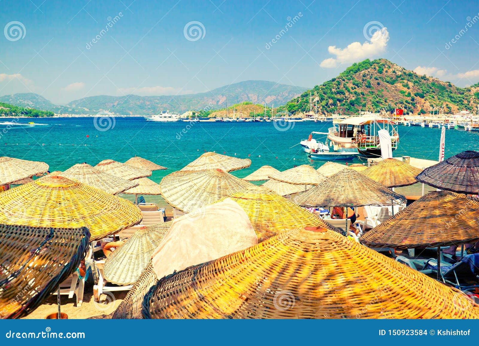 Malerische Weidenstrandschirme auf sonnigem Strand von türkischem Riviera
