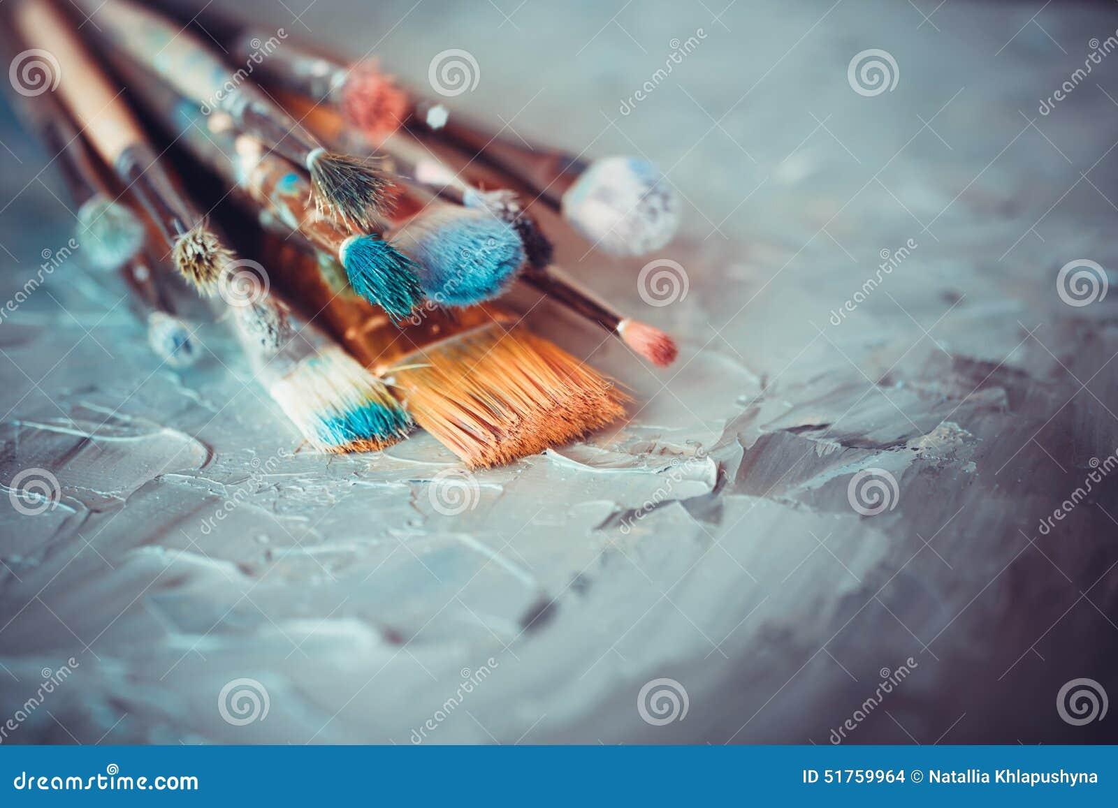 Malerpinsel auf dem Künstler mit einer Plane bedeckt mit Ölfarben