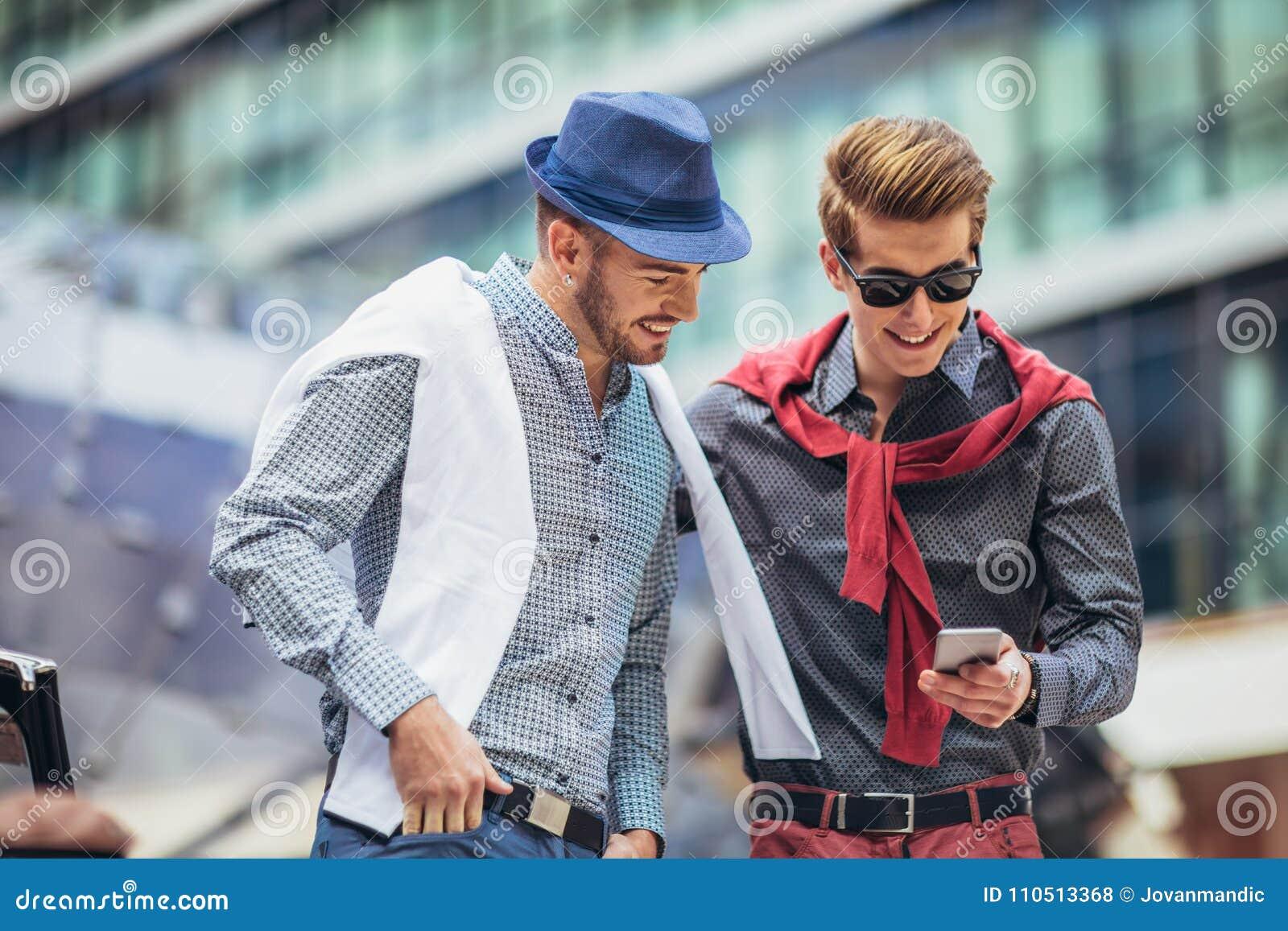 Beautiful models outdoors using phone, city style fashion