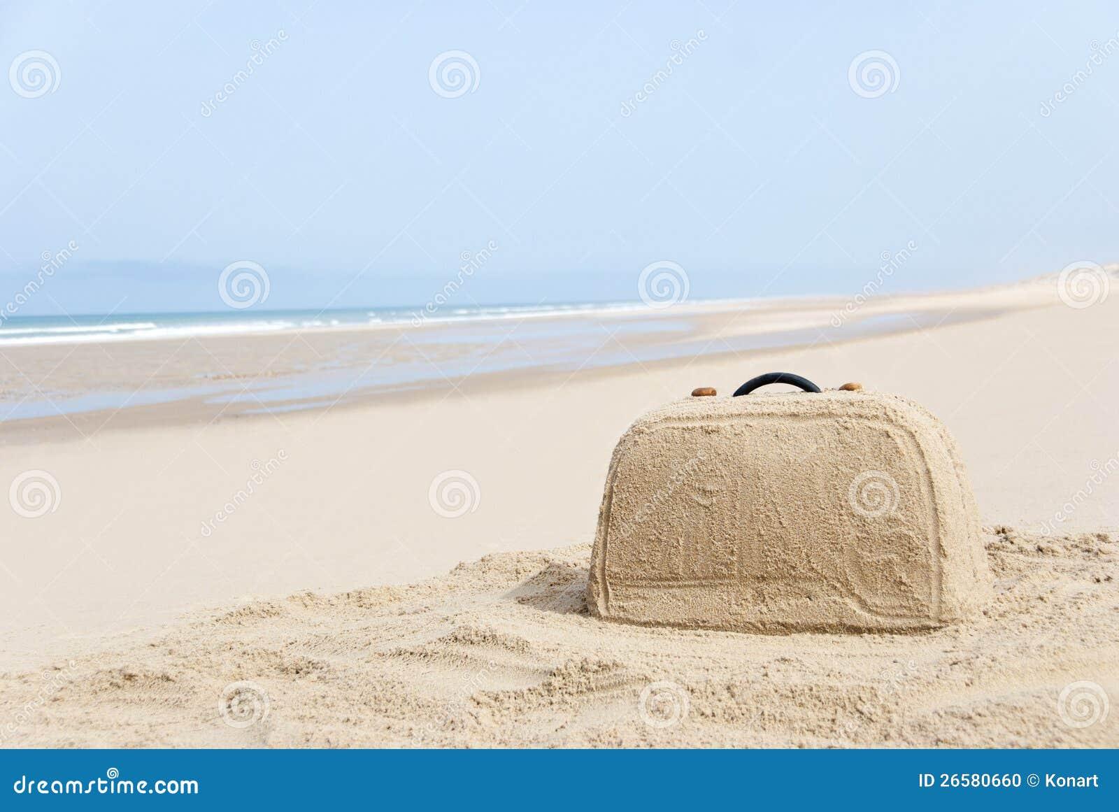 Maleta hecha fuera de la arena en la playa
