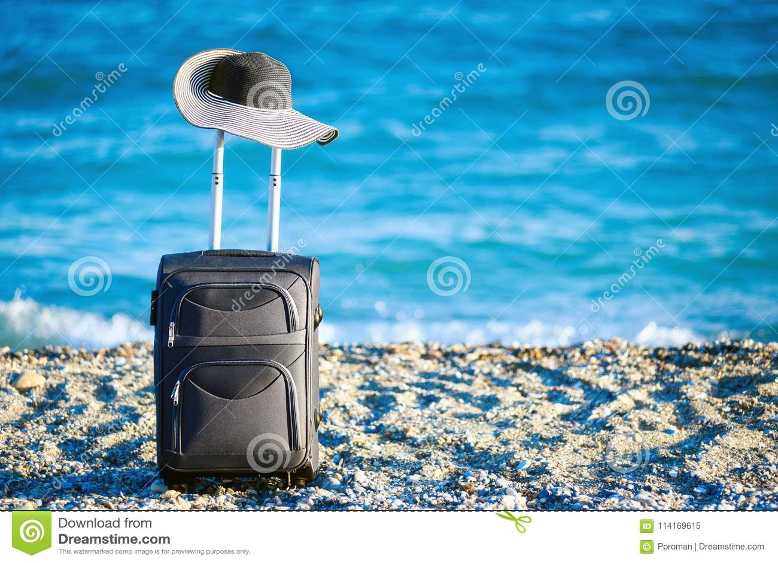 Maleta y sombrero en la playa