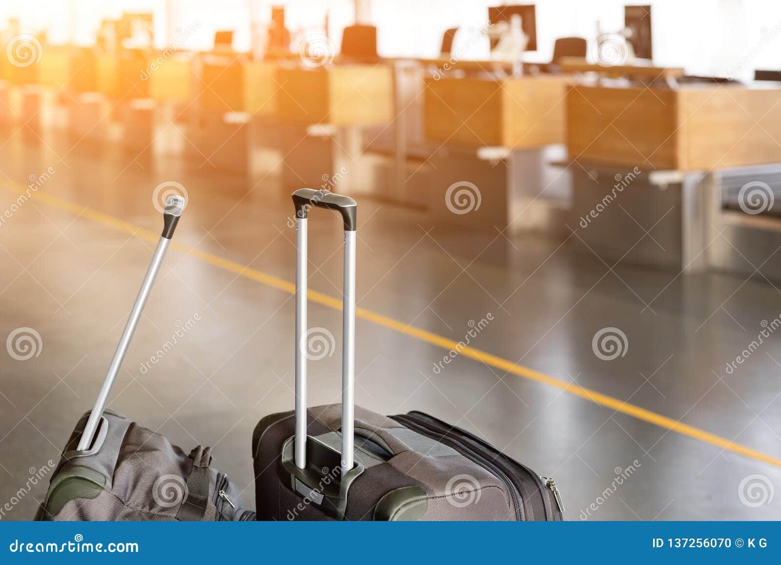 Maletas del equipaje en el terminal de aeropuerto con el mostrador de facturación vacío