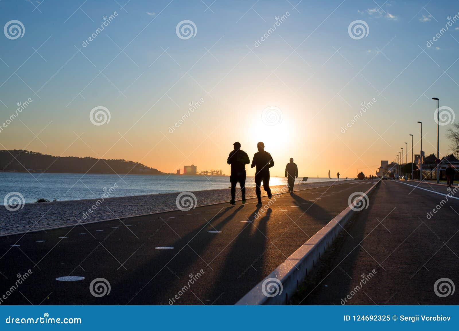 Malhar o fundo, dois povos que movimentam-se na margem no por do sol, silhuetas dos corredores, conceito saudável do estilo de vi