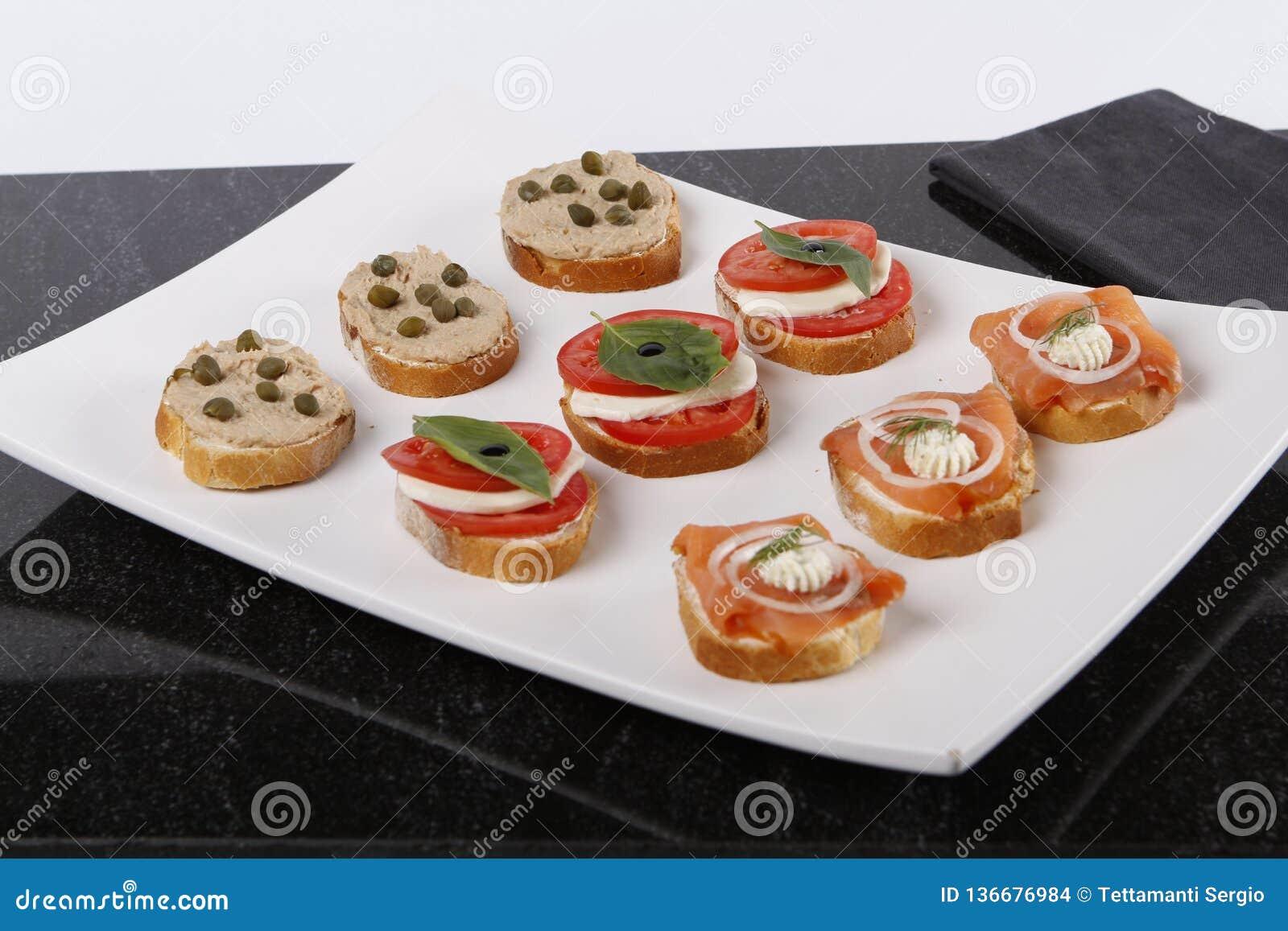 Mali canapes z tuńczykiem, kapar, pomidor, mozarella, łosoś i cebule,