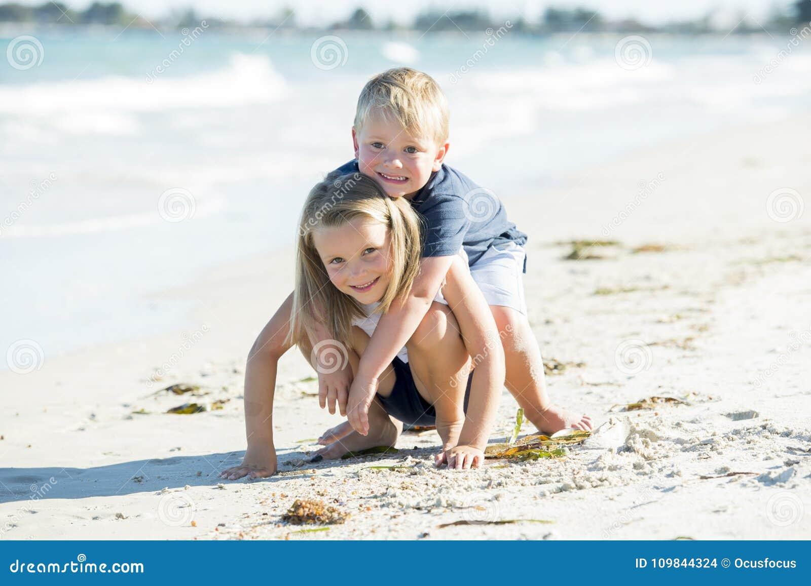 Mali uroczy i słodcy rodzeństwa bawić się wpólnie w piasek plaży z małym bratem ściska jego pięknego blond młodego siostrzanego e