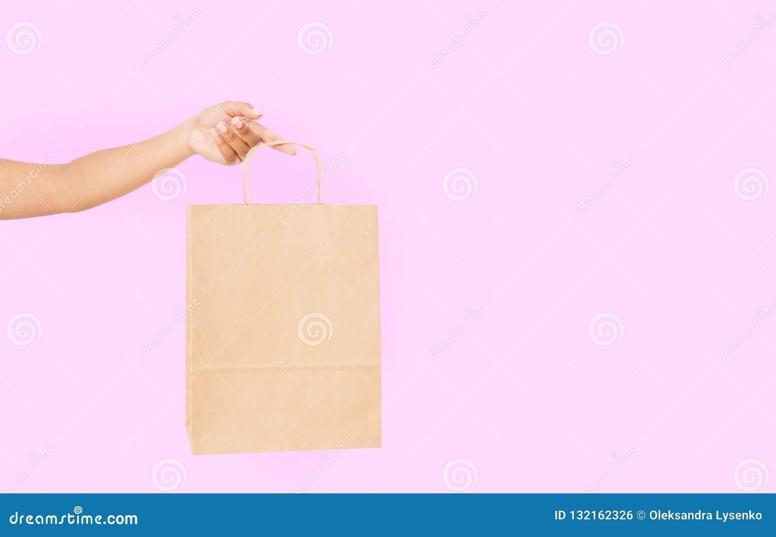 Mallmellanrumspacke Afrikansk amerikankvinnahand som rymmer en pappers- kraft påse på rosa bakgrund Leverans och shopping