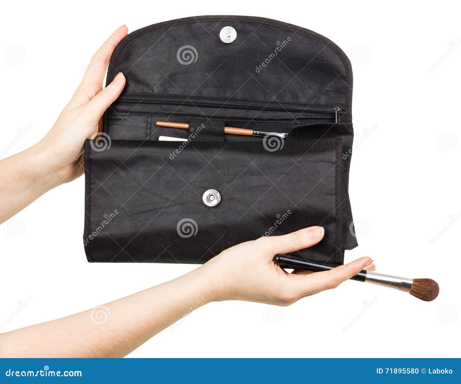 Malote levando com as escovas para a composição nas mãos fêmeas