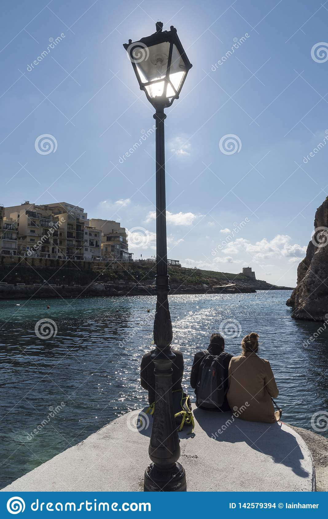 Sun Worship and lamp post on the jetty in Xlendi
