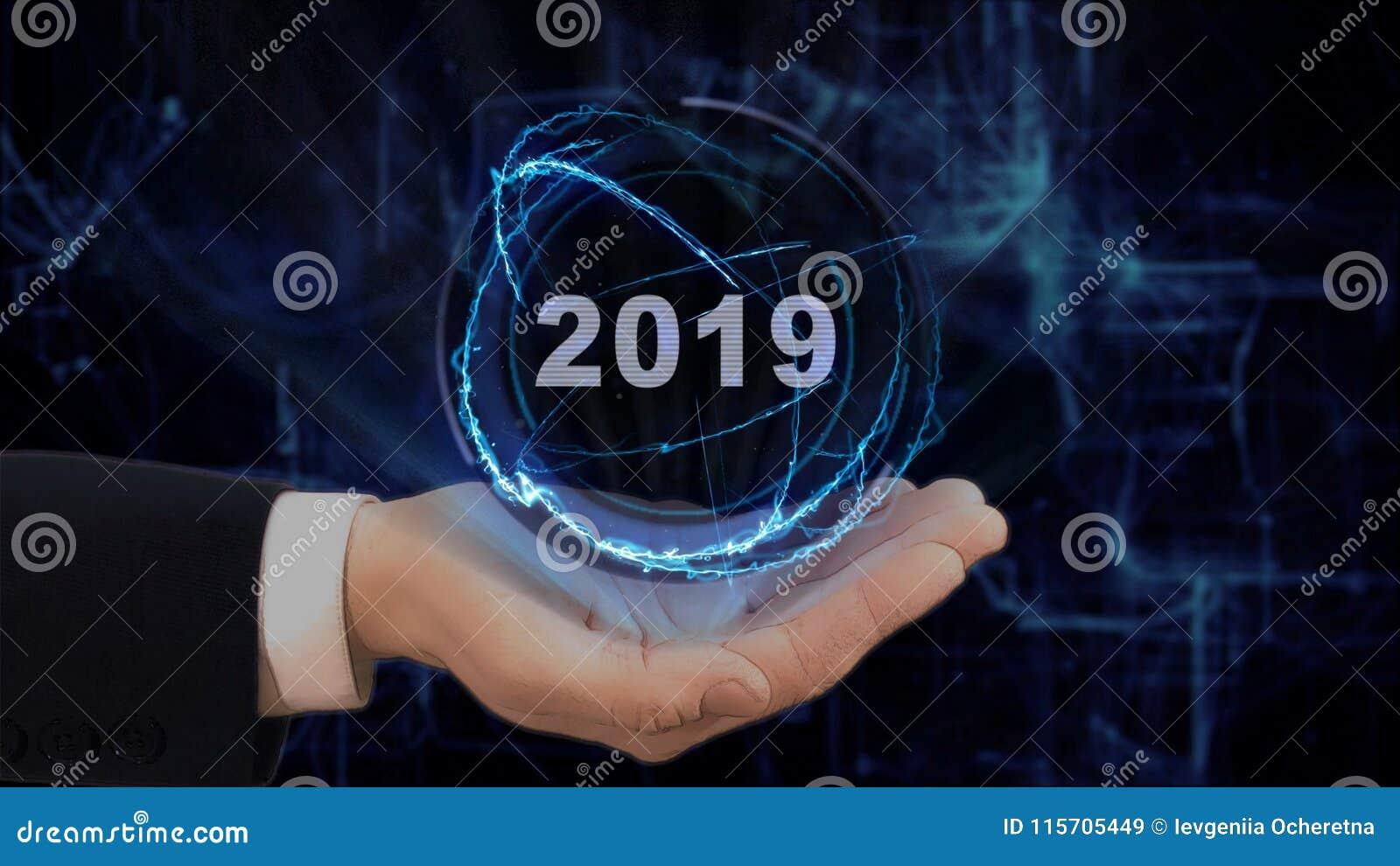 Malująca ręka pokazuje pojęcie hologram 2019 na jego ręce