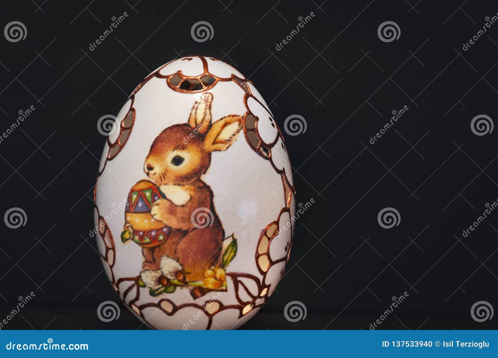 Malujący i rzeźbiący Easter jajko na czarnym tle