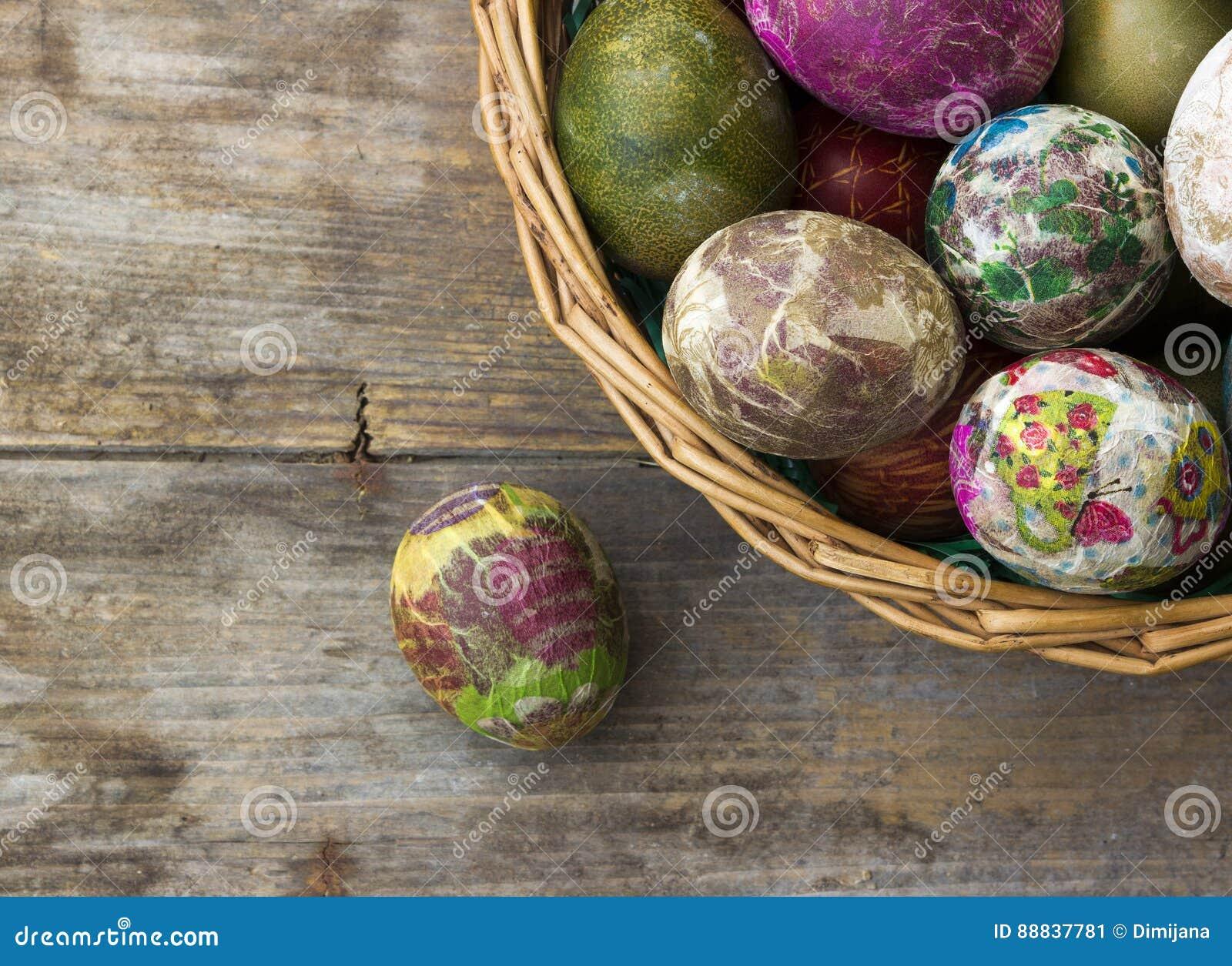 Malujący Wielkanocni jajka koszykowi na drewnianym tle