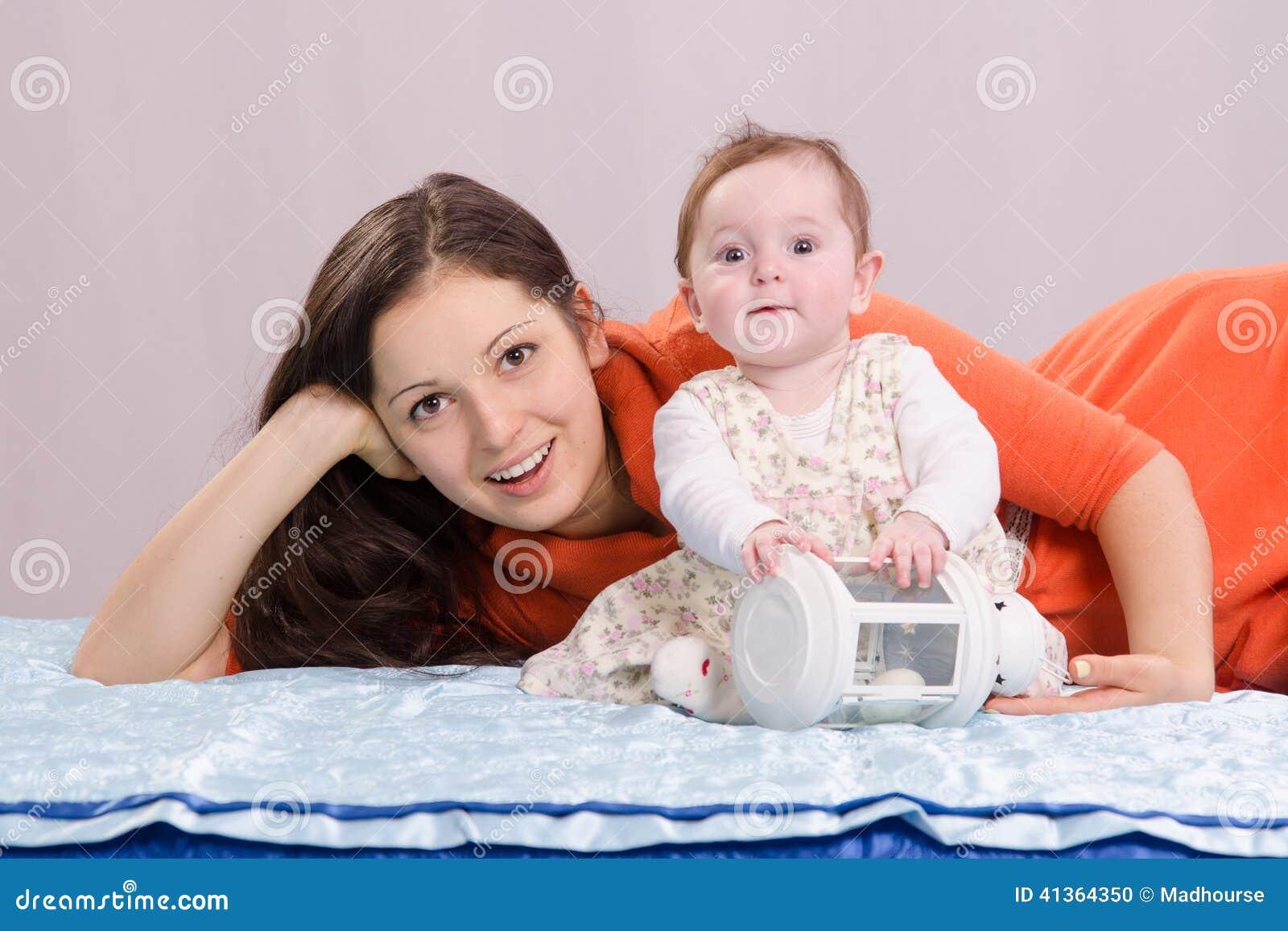 Mamá con una hija de seis meses que juega en la cama
