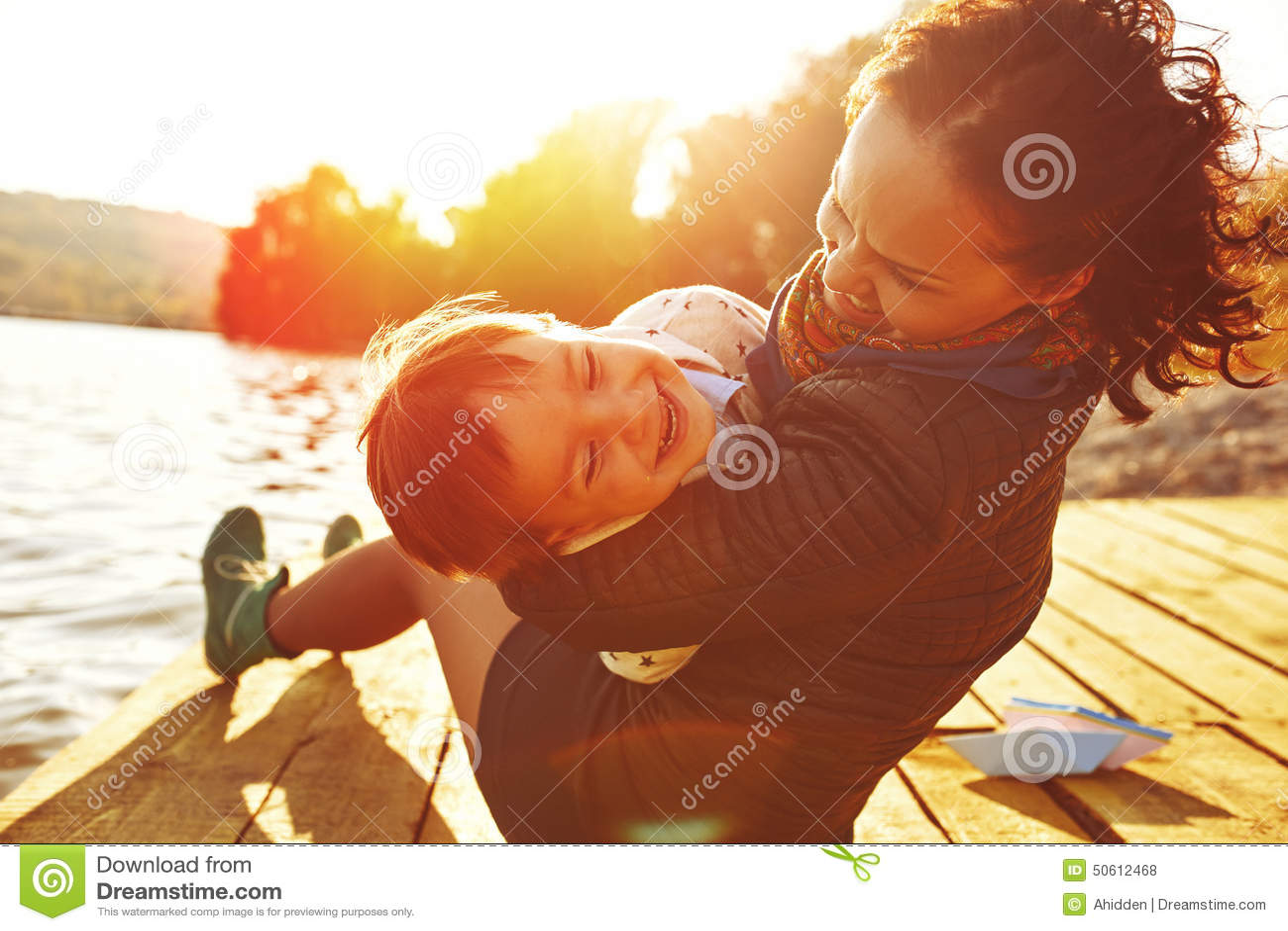 Mamá e hijo que se divierten por el lago