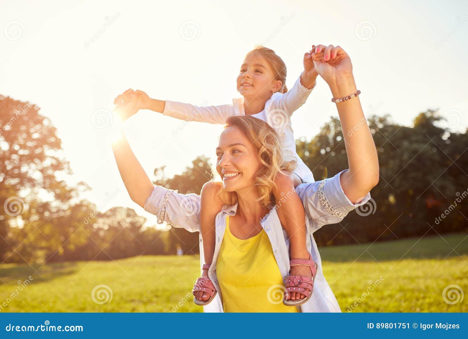 Mamá que detiene a la hija en hombros