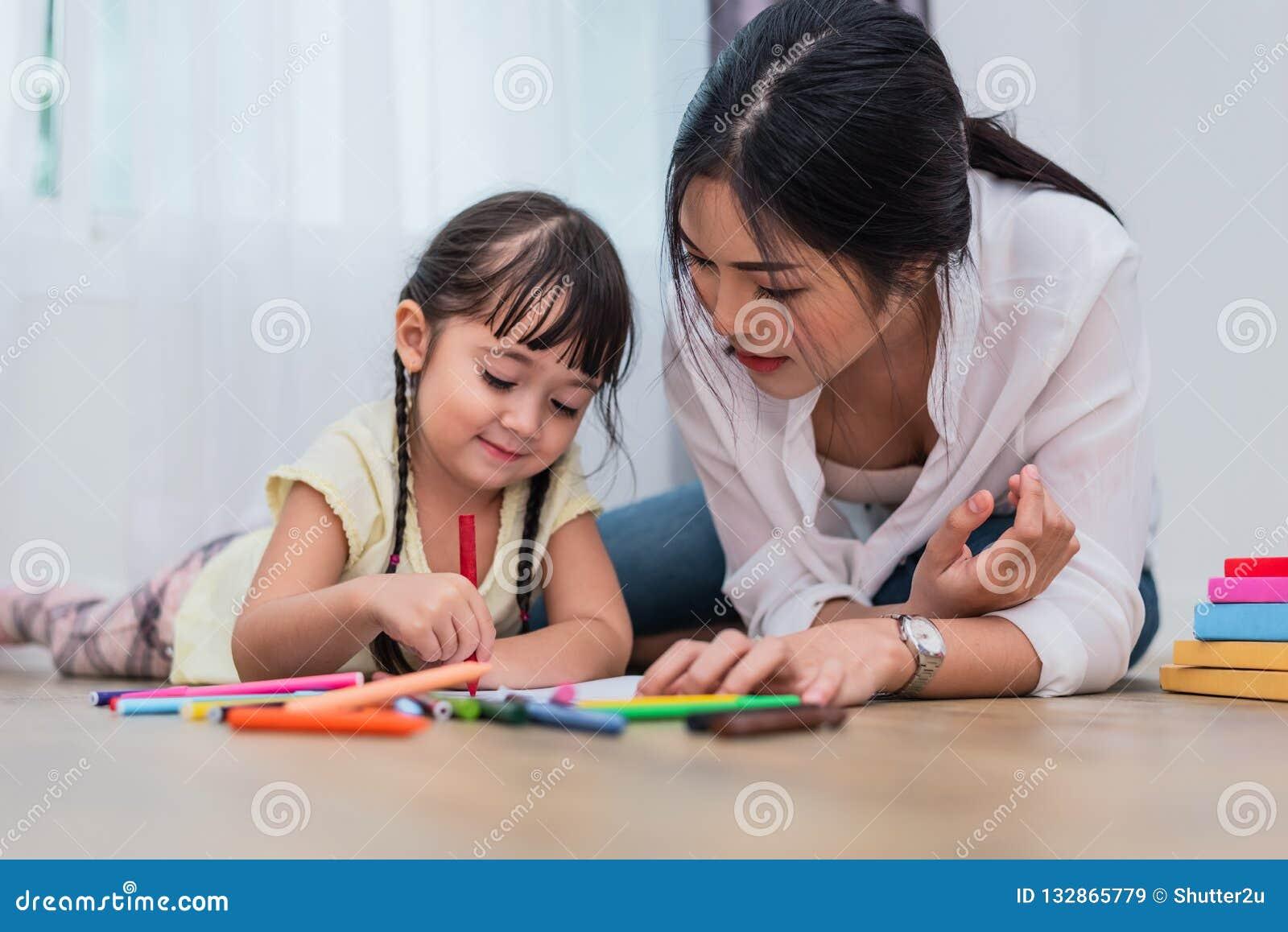 Mamá que enseña a su hija al dibujo en clase de arte De nuevo a schoo