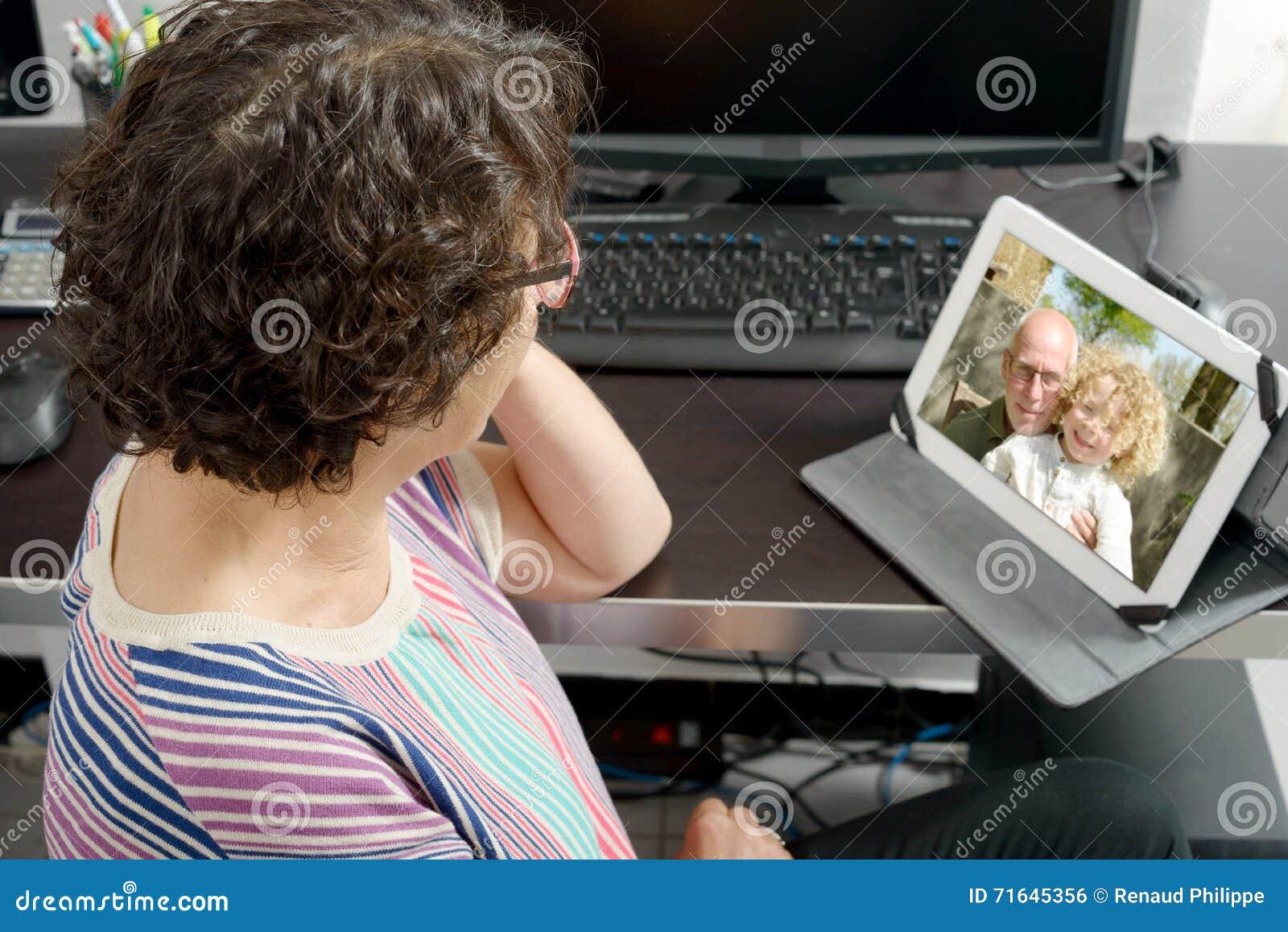 Mamá que hace una llamada distante en Internet