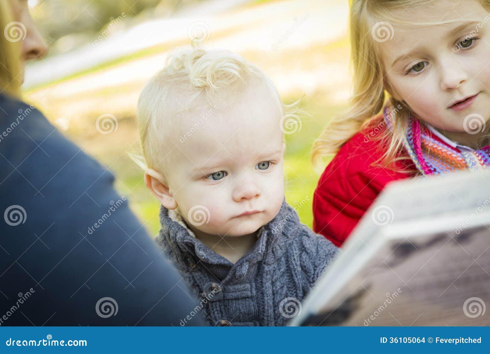 Mamá que lee un libro a sus dos niños rubios adorables