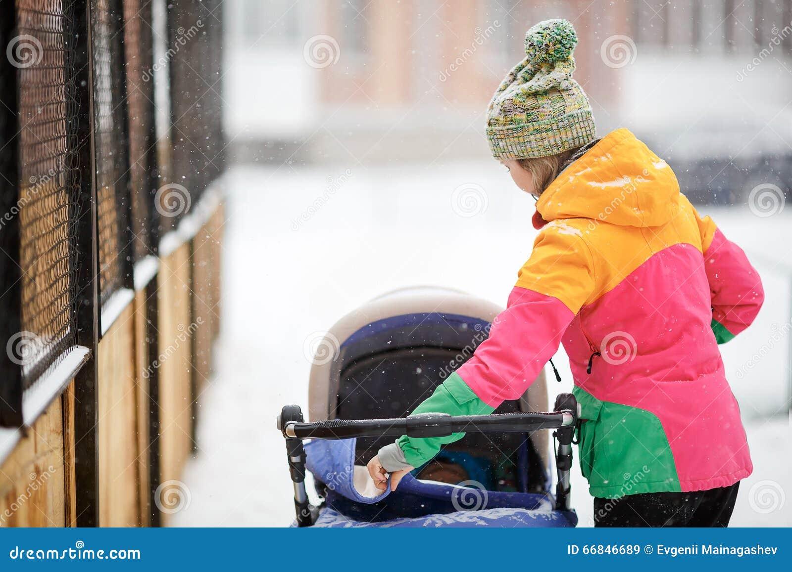 Mamá y bebé en cochecito en el paseo, tiempo nevoso del invierno Nevadas, ventisca, al aire libre