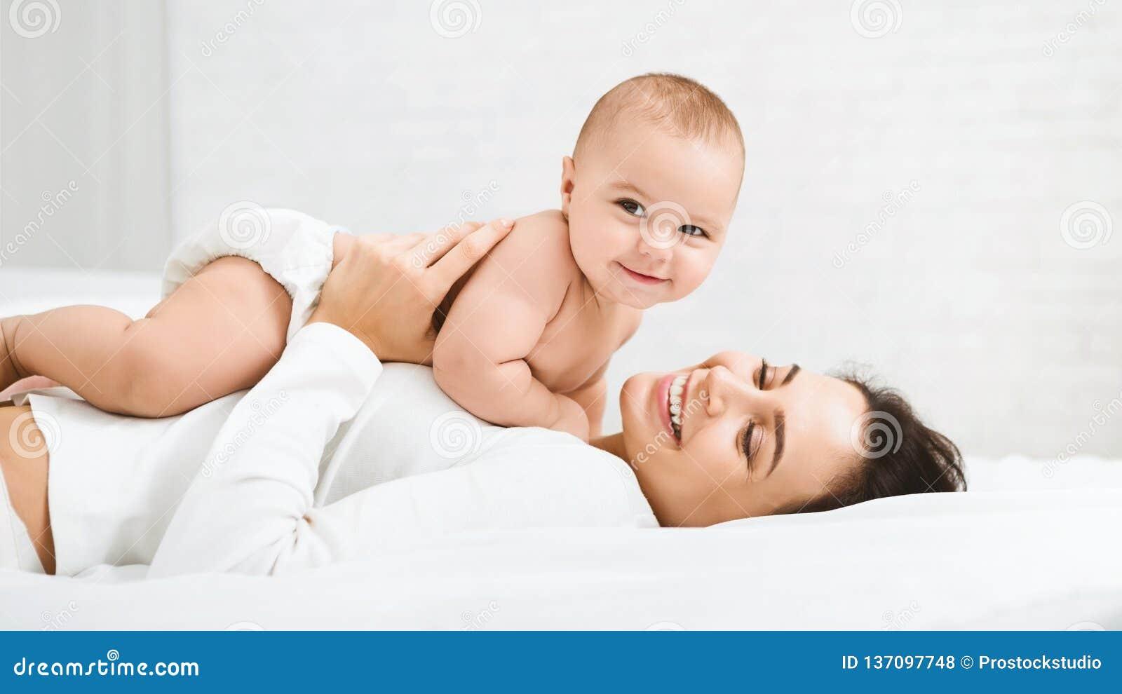 Mamá y bebé en el pañal que juega en dormitorio