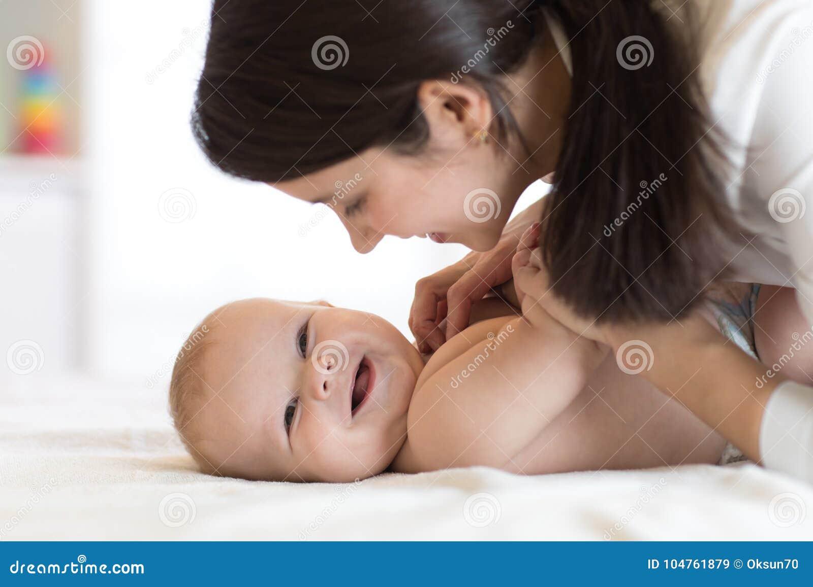 Mamá y bebé en el pañal que juega en dormitorio soleado Madre y pequeño niño que se relajan en casa Una muchacha hermosa de la ra