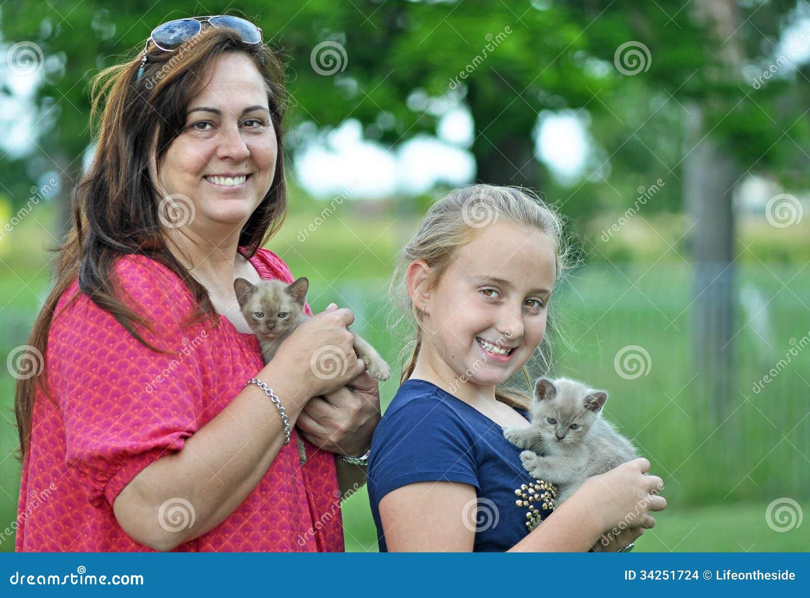 Mamá y hija sonriente alegre y nuevos gatitos del animal doméstico