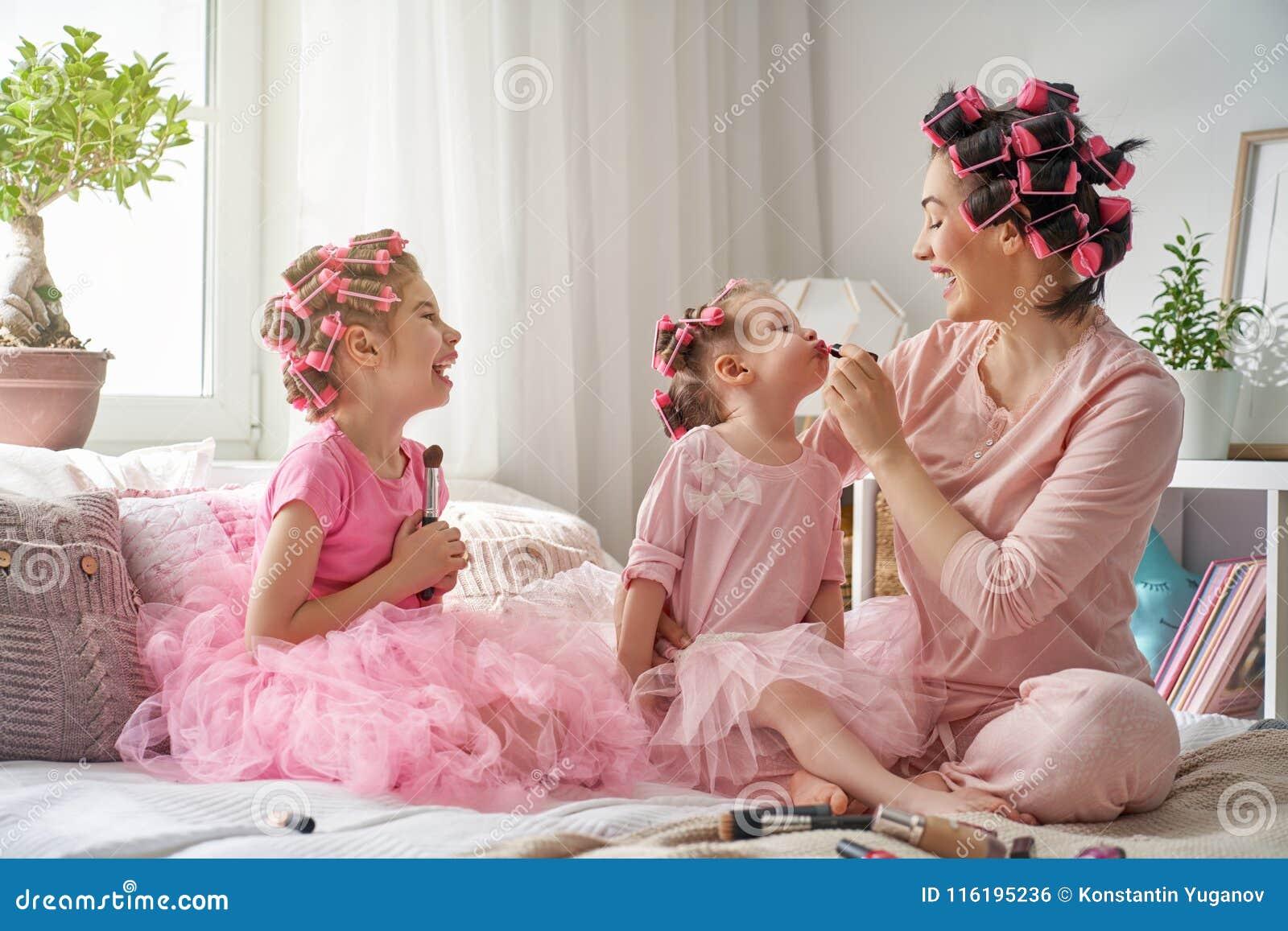 Mamá y niños que hacen maquillaje