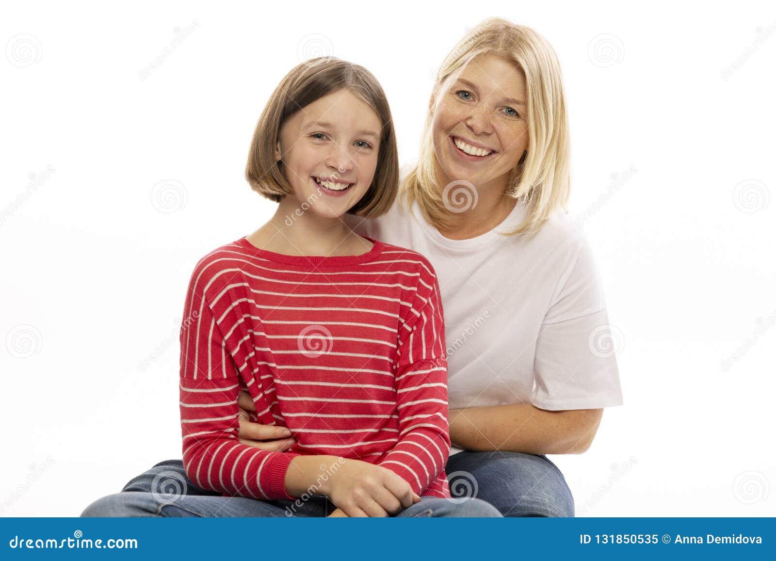 Mamã com sua filha adolescente que abraça e que ri
