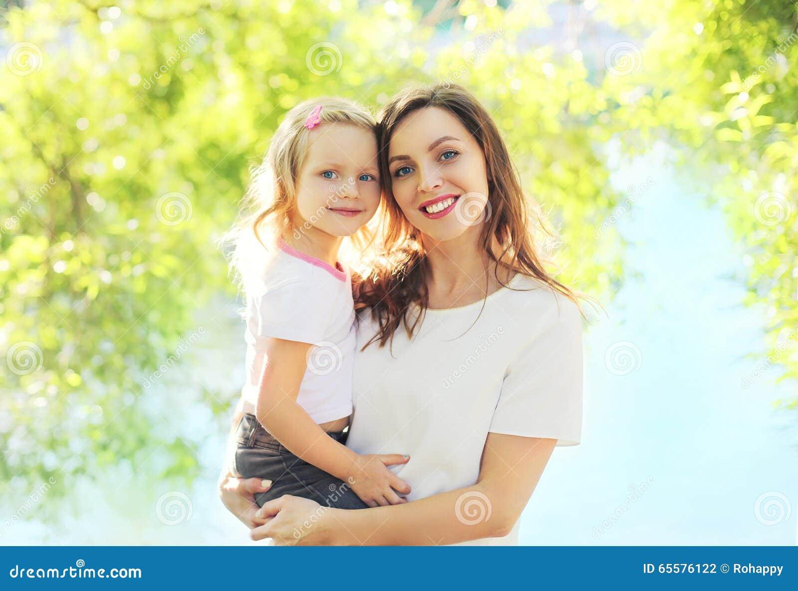 Mamã de sorriso feliz do retrato que abraça a filha da criança no verão