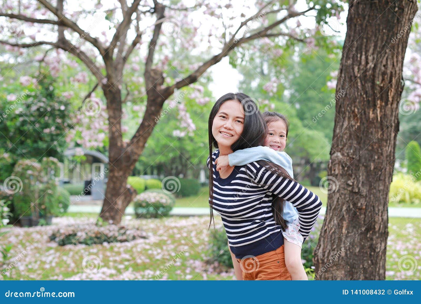 Mamã de sorriso que leva sua menina da criança pequena no jardim com inteiramente a flor do rosa da queda ao redor Família loving