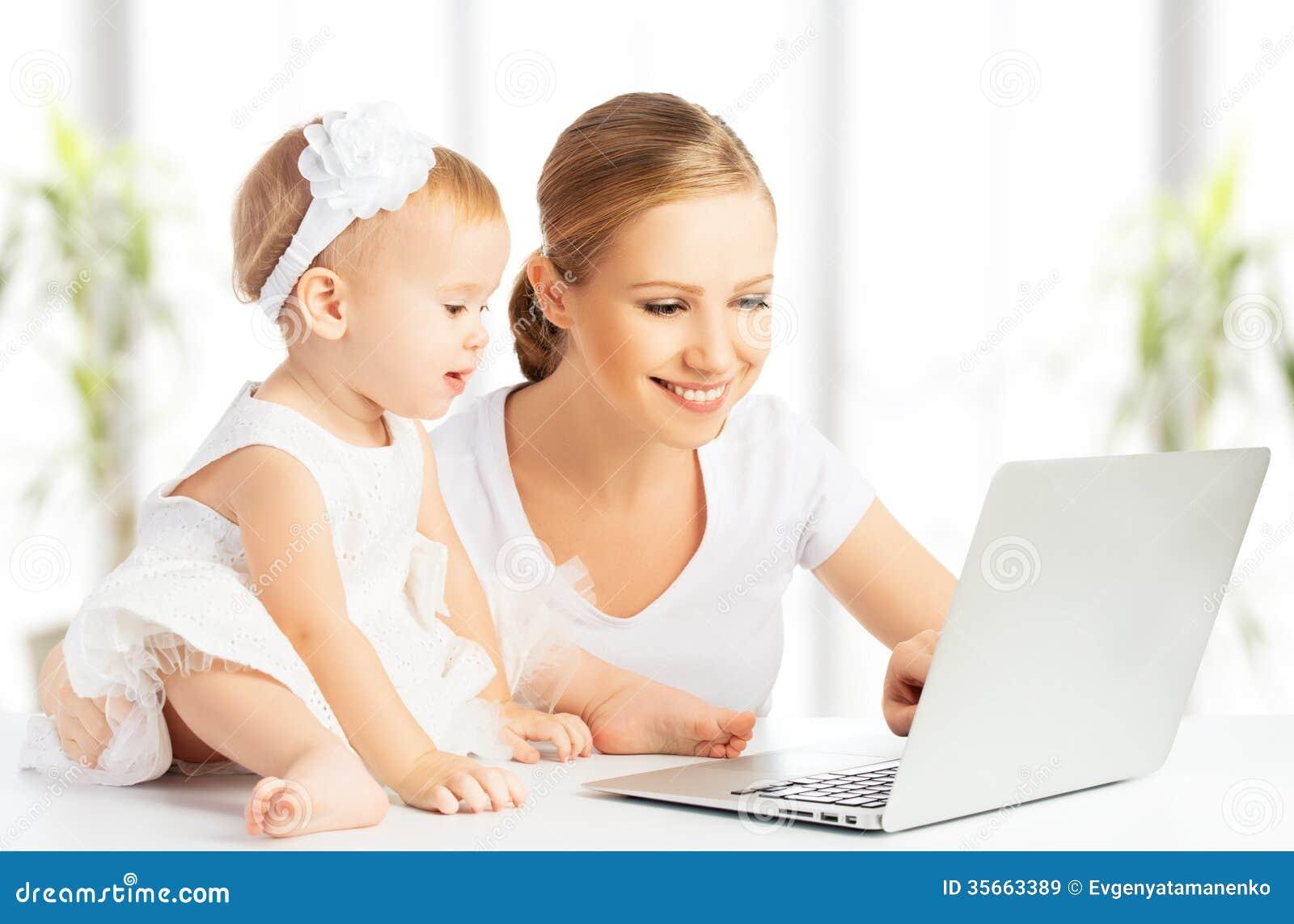 Mamã e bebê com o computador que trabalha da casa