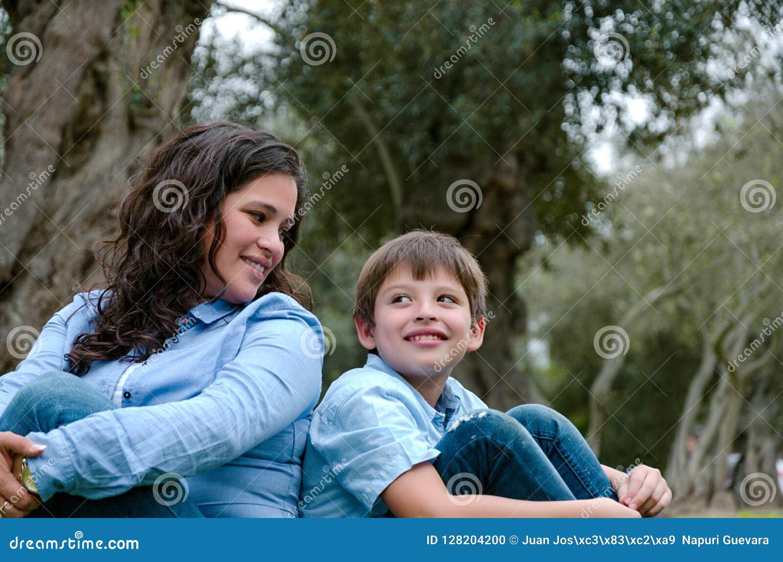 Mamã e filho que sentam-se na grama verde no parque verde Conceito de relações de família felizes