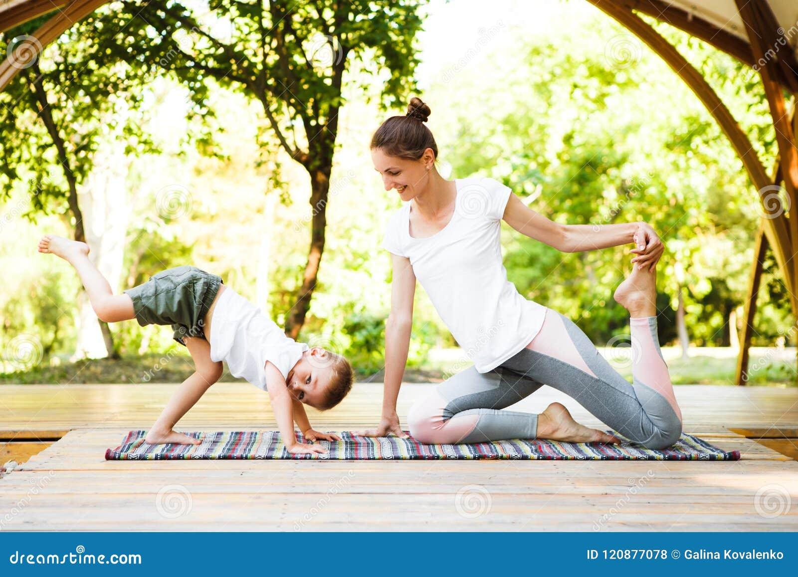 A mamã e o filho estão praticando a ioga no parque
