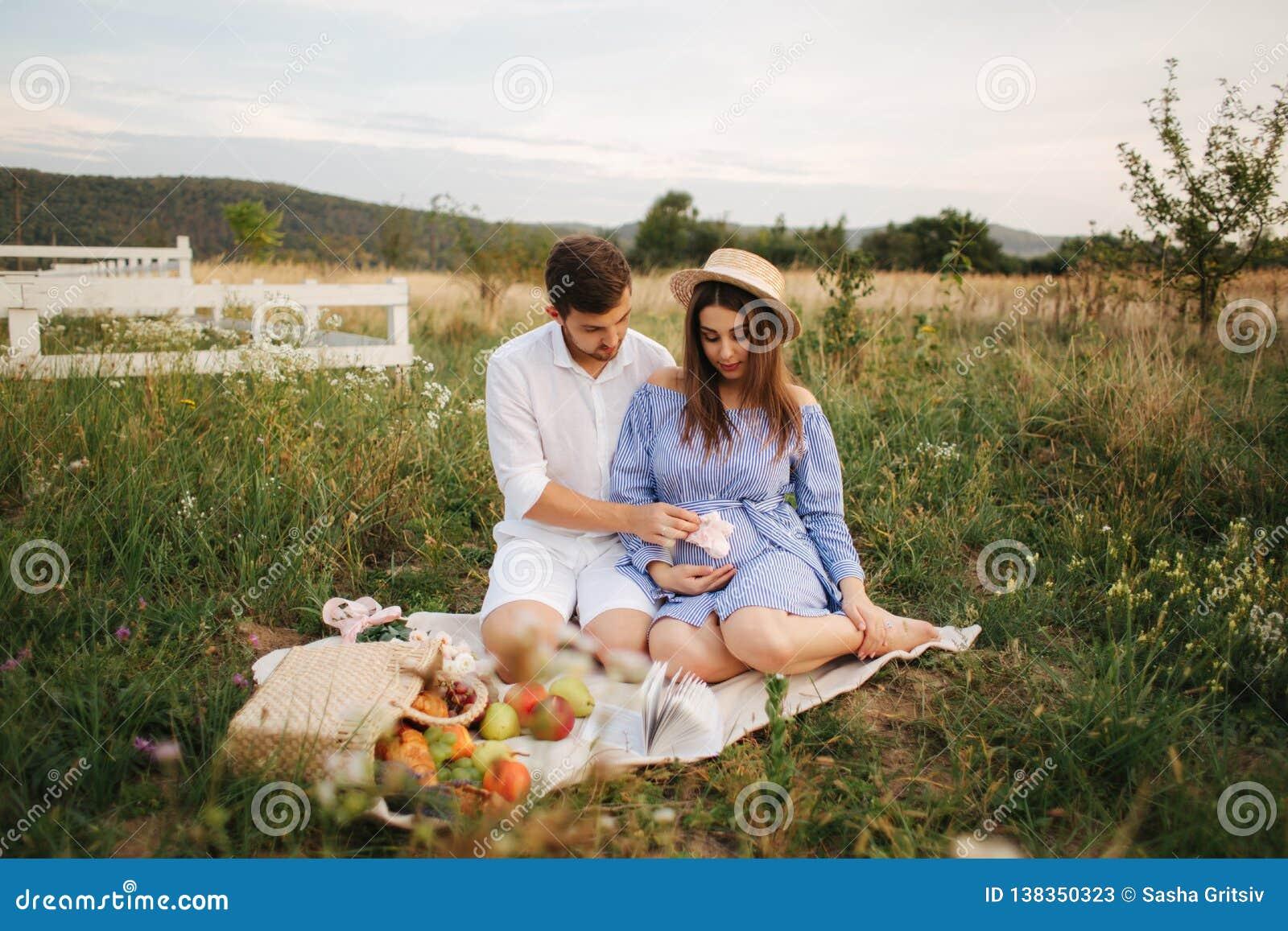 A mamã e o paizinho futuros sentam-se no campo A mulher gravida com seu marido pôs suas mãos sobre a barriga