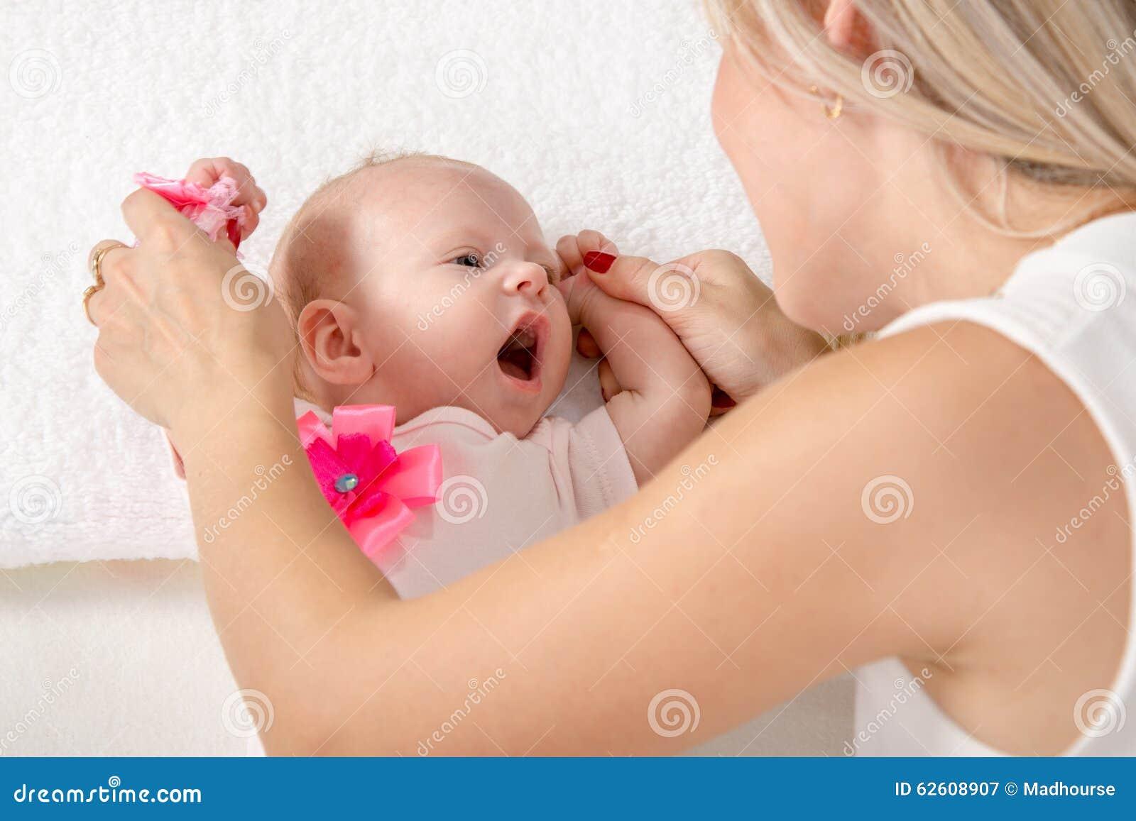 A mamã está olhando uma menina de dois meses com uma boca aberta