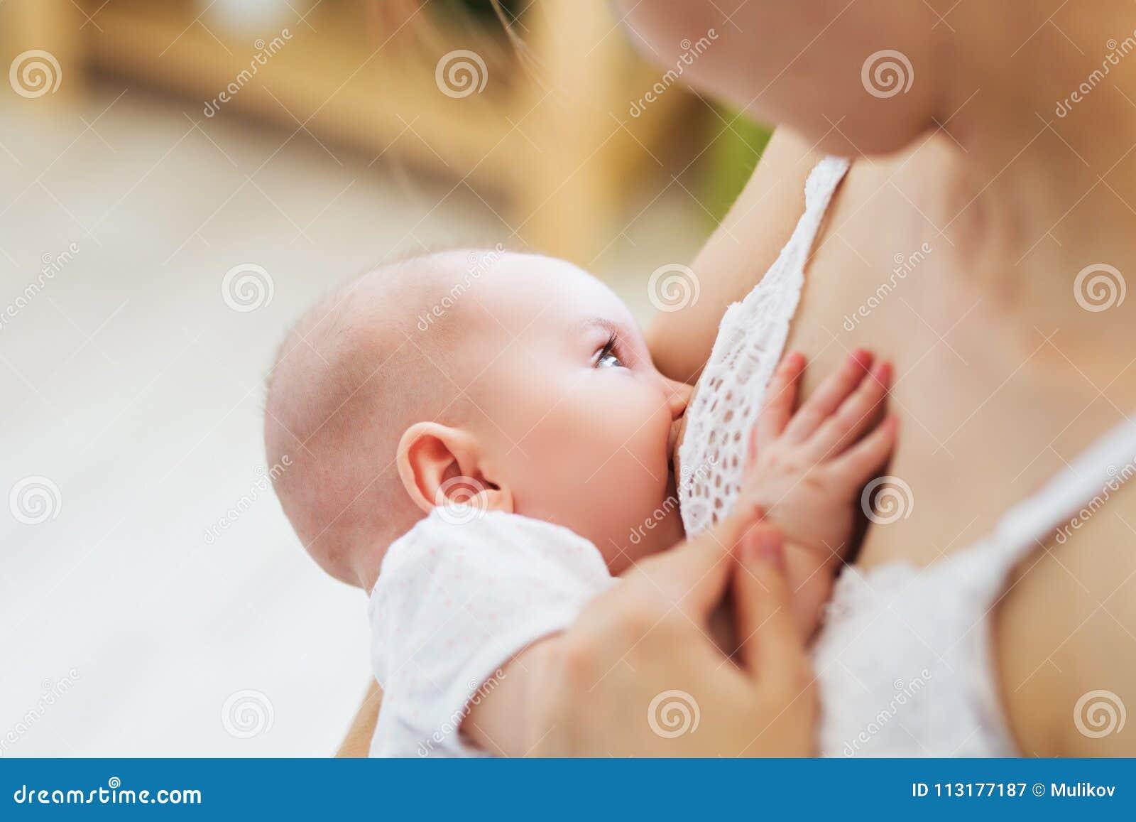 Mamã nova que amamenta sua criança recém-nascida Conceito do infante do fluxo de leite Sira de mãe alimentam sua filho ou filha d