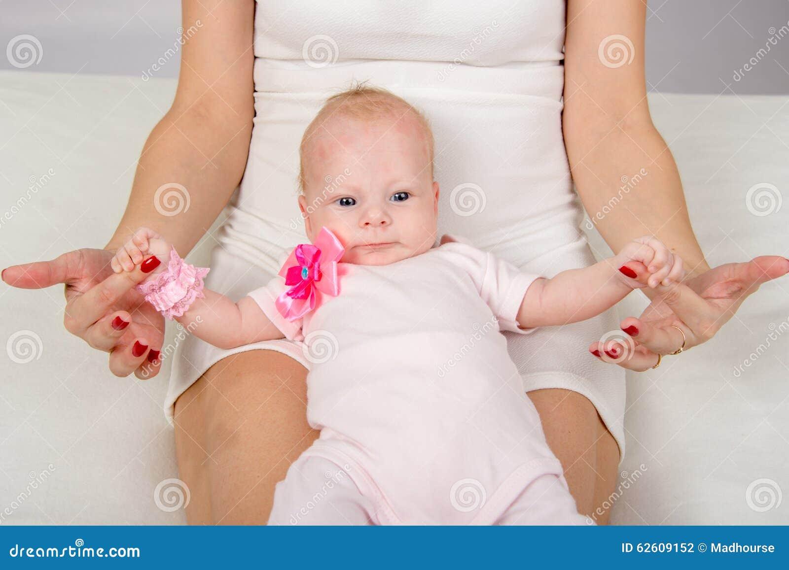 A mamã pôs um bebê de dois meses sobre seus joelhos e guardar sua pena