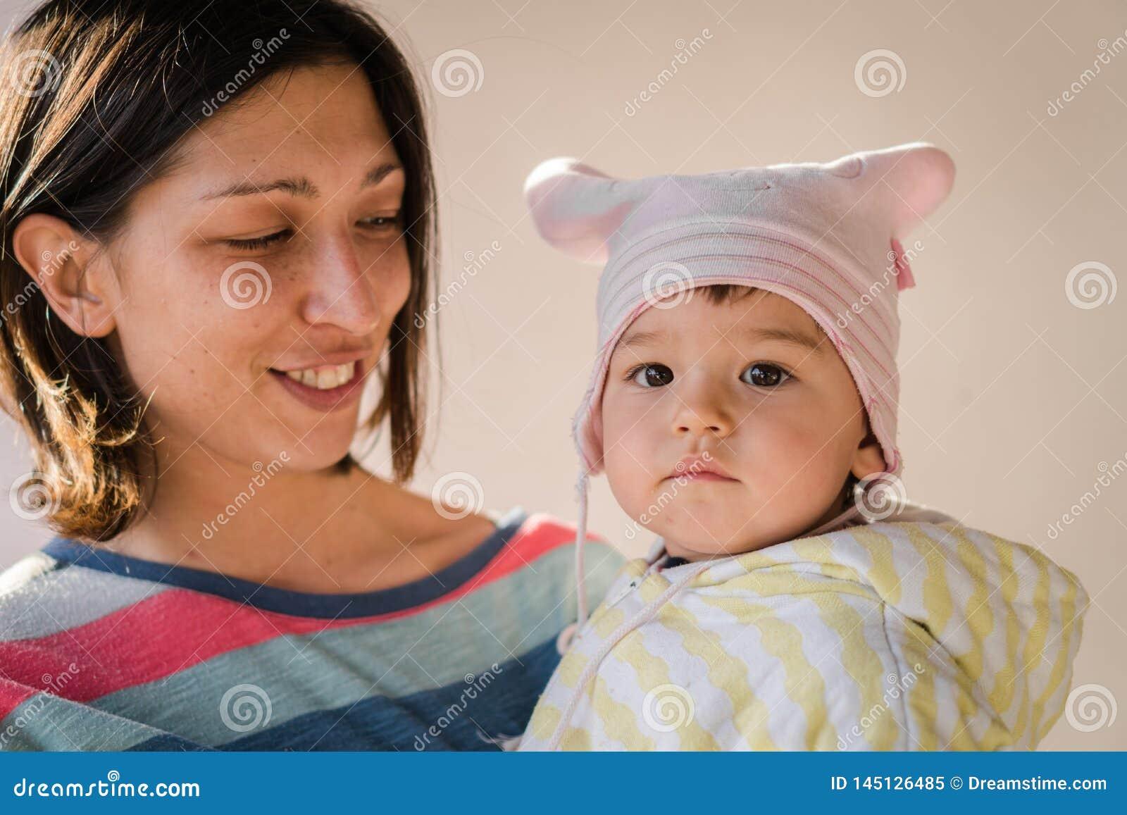 Mamã que guarda a criança pequena feliz
