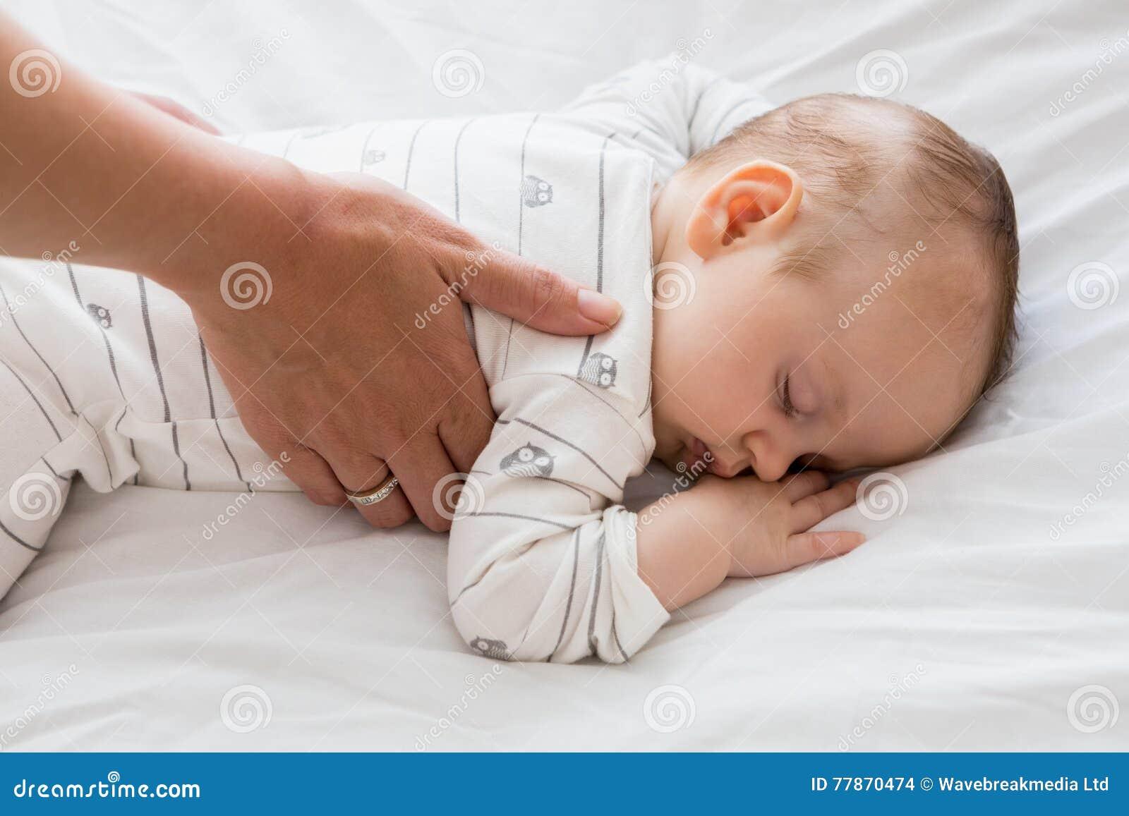 Mamã que põe o bebê para dormir na cama de bebê
