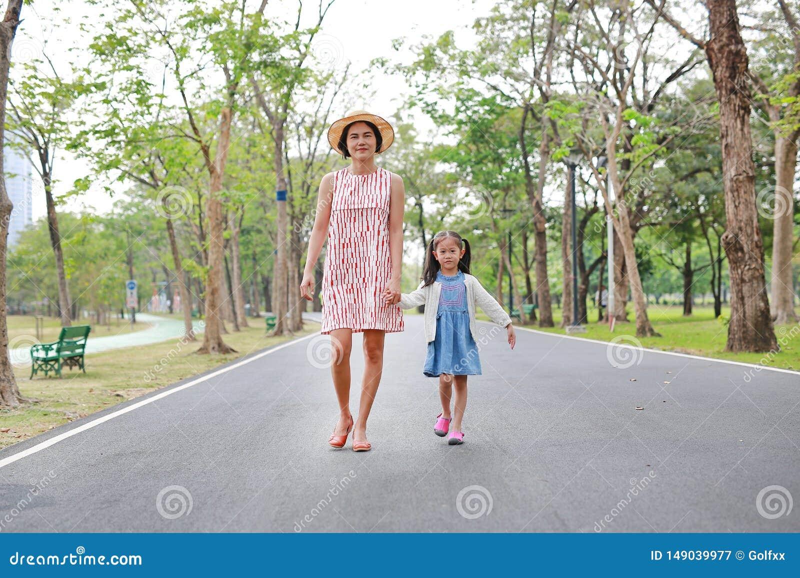 Mam? feliz e filha asi?ticas que andam na rua no parque do ver?o