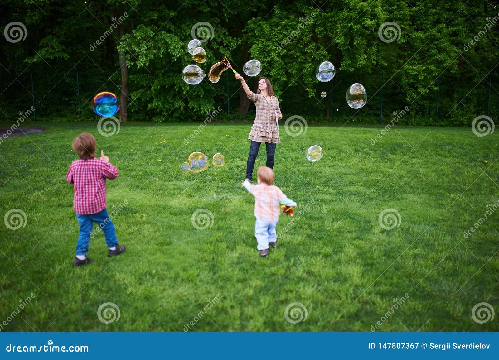 Mam? y ni?os que juegan burbujas de jab?n en el c?sped verde en el parque