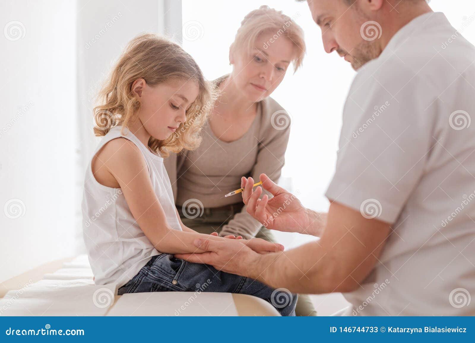 Mama i chłopiec podczas szczepień przy pediatrą