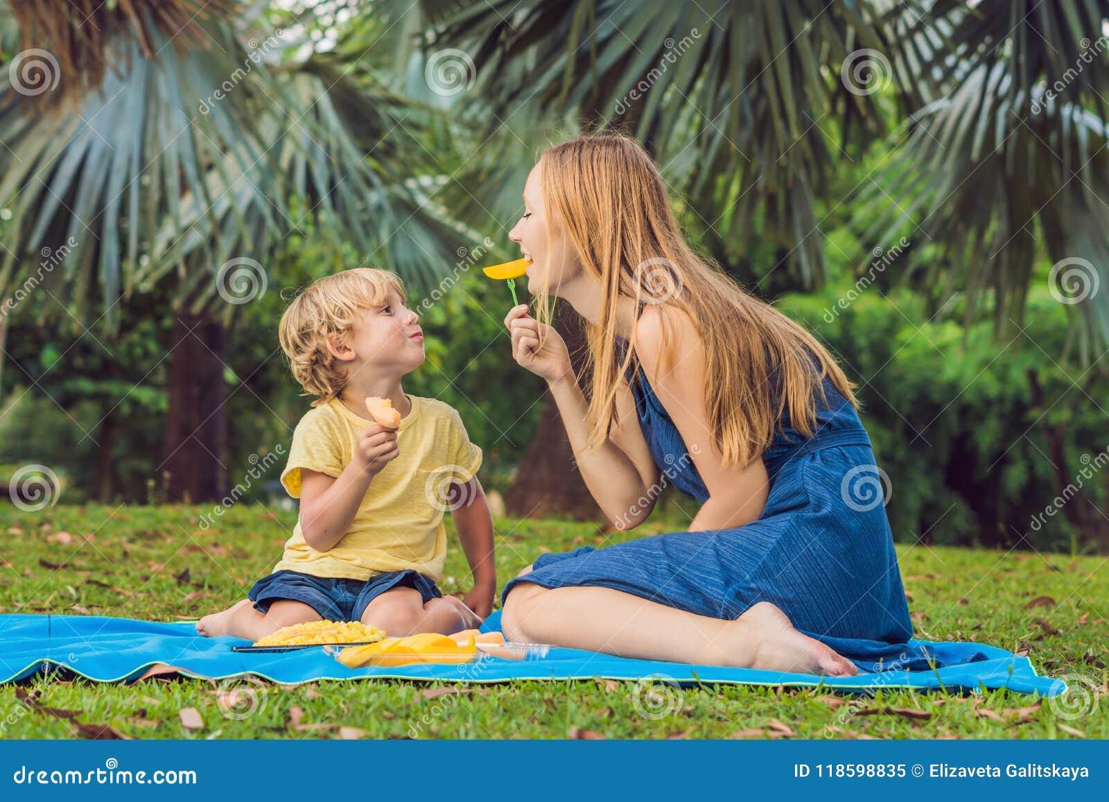Mama i syn pinkin w parku Je zdrowe owoc - mango